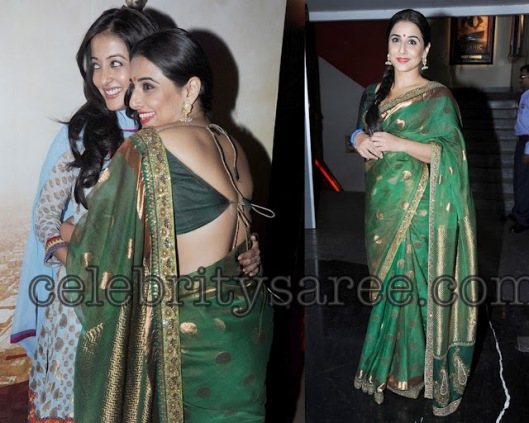 green silk traditional sabyasachi saree with gold polka dots all over saree paired with matching short sleeves back less saree blouse.